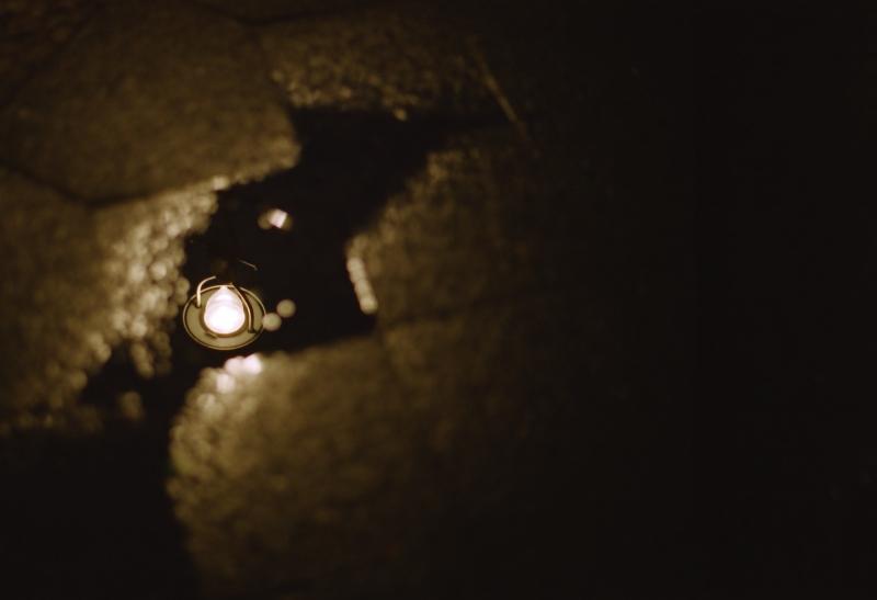 Spiegelung einer Lampe in einer Pfütze