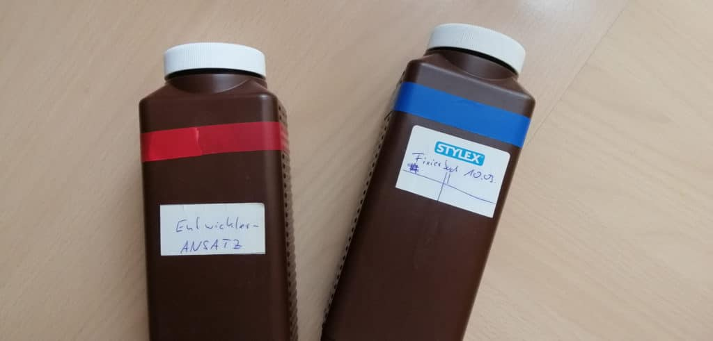 Zwei braune Laborflaschen, eine mit rotem und eine mit blauem Klebeband umwickelt.